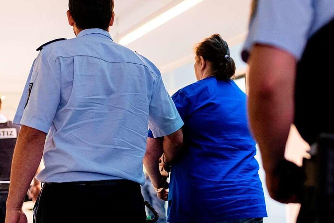 Justizbeamte bringen Berrin T. nach der Urteilsverkündung aus dem Gerichtssaal.  | Foto: dpa