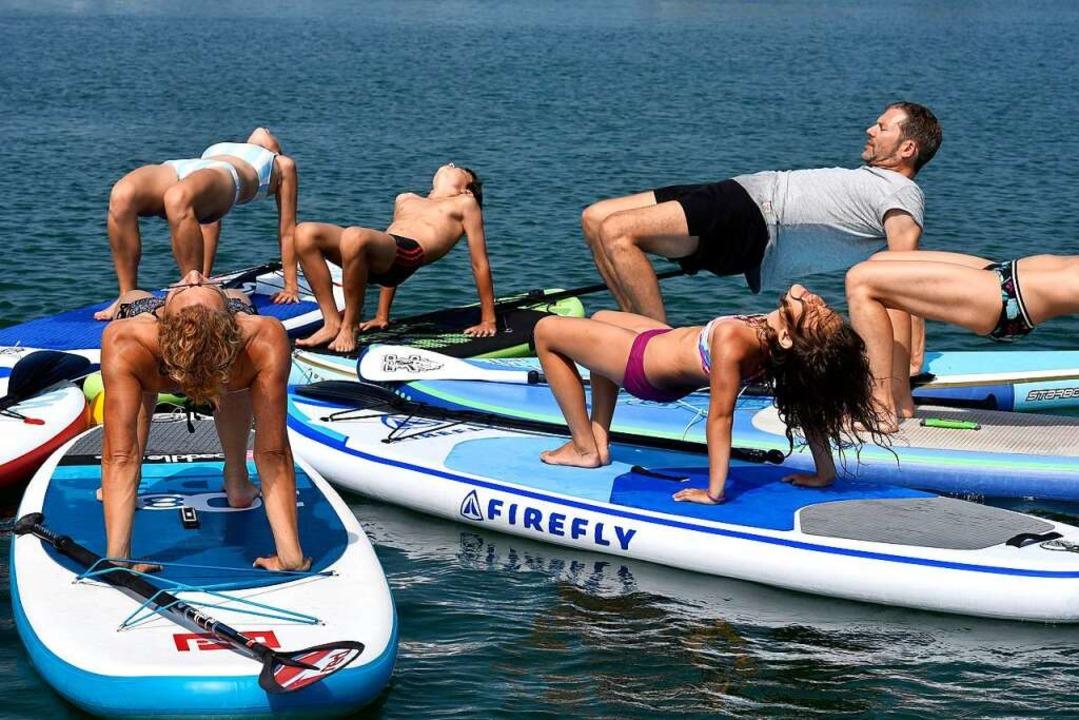 Dietmar Oliver Küther (rechts im T-Shi...bei Yoga-Übungen auf den Surfbrettern.  | Foto: Thomas Kunz