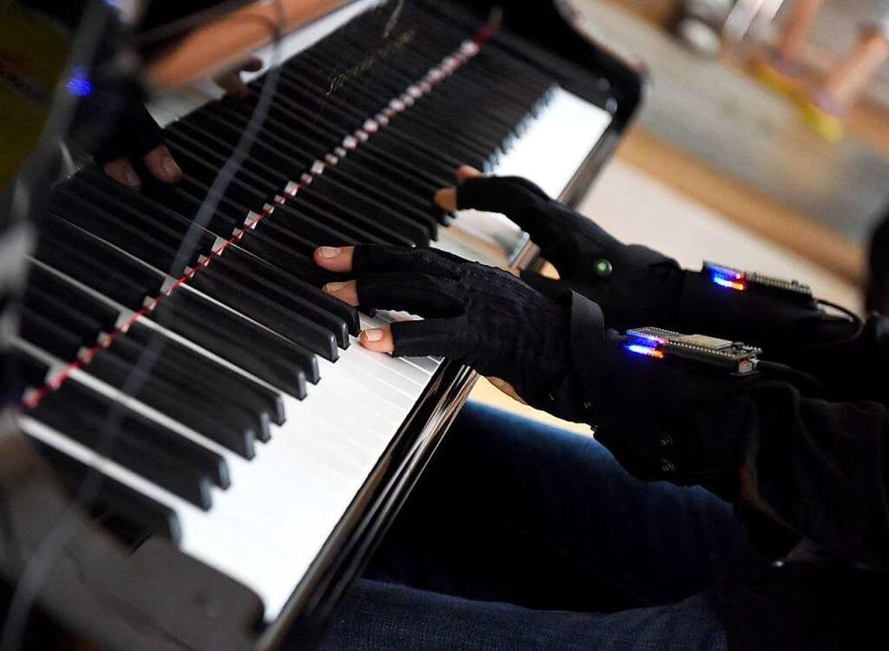 Die Datenhandschuhe lassen die Finger frei zum Klavierspielen.  | Foto: Rita Eggstein