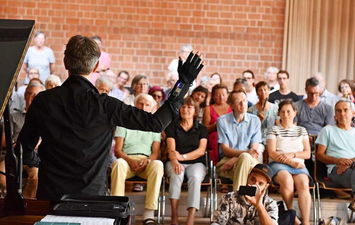 Ralf Schmid  hebt vor den Gästen die Hand – und es ertönt ein Klang.  | Foto: Rita Eggstein