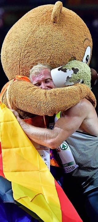 Arthur  Abele  freut sich in den Armen...chen Berlino über die Goldmedaille.     | Foto: AFP