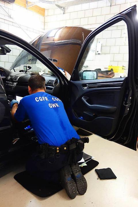 Ein Spezialist durchsucht ein Auto.  | Foto: Felix Held