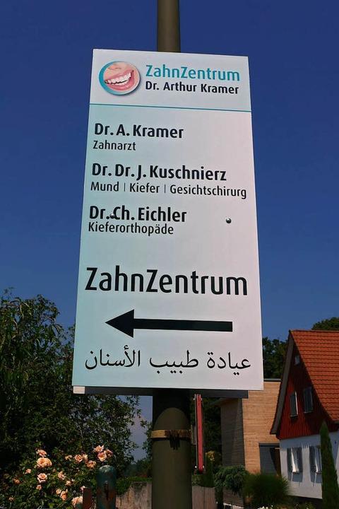 Ein Schild weist die Zahnarztpraxis auch auf Arabisch aus.  | Foto: Nikola Vogt