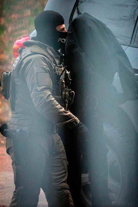 Nach seiner Festnahme wird Dasbar W.  ...olizisten  aus einem Fahrzeug geführt.  | Foto: Christoph Schmidt