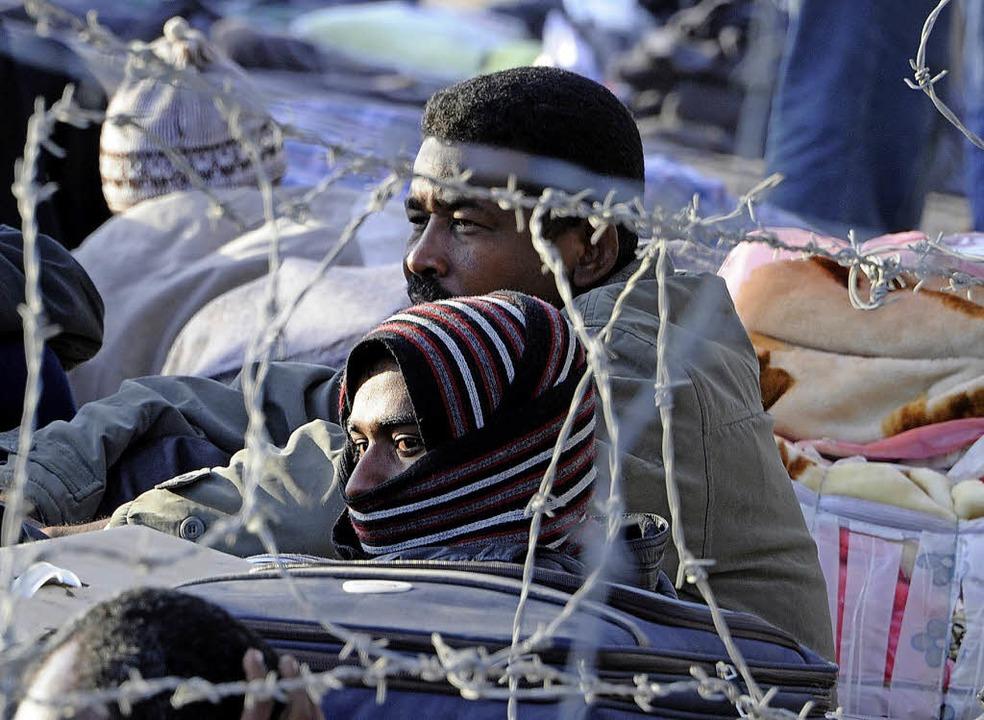 Afrikanische Flüchtlinge in einem libyschen Lager hinter Stacheldraht.   | Foto:  AFP