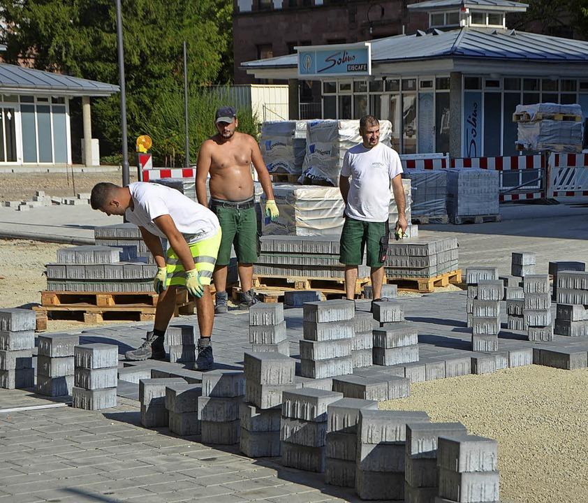 Auf ein Neues: Arbeiter verlegen das  Pflaster auf dem Platz.  | Foto: Walser