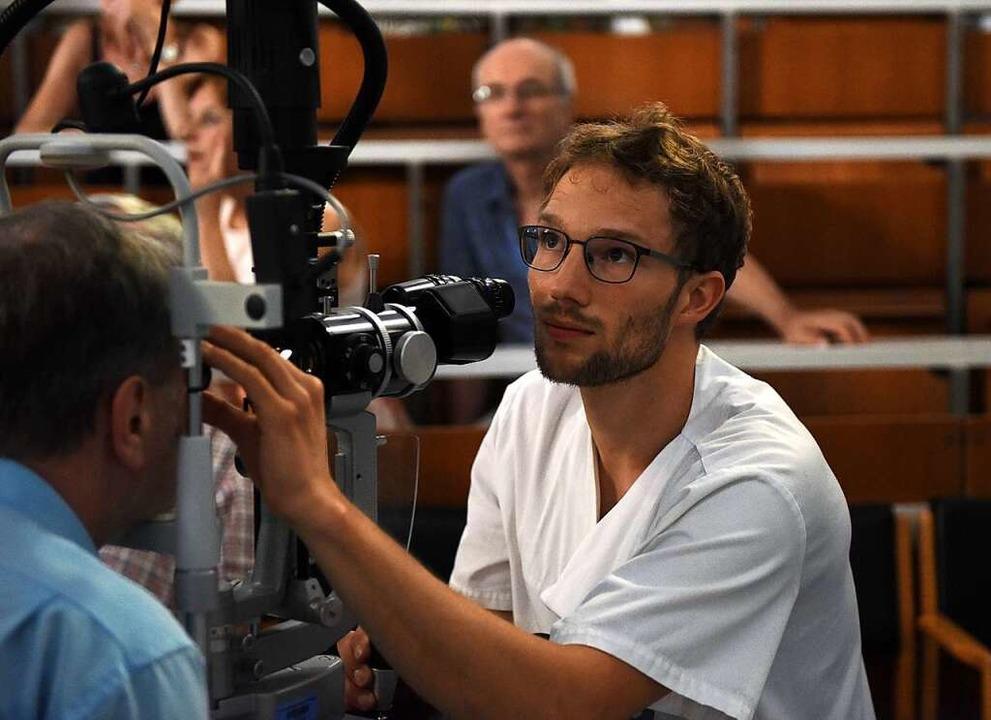 Markus Gruber (rechts) untersucht eine...r der BZ-Ferienaktion am rechten Auge.  | Foto: Rita Eggstein