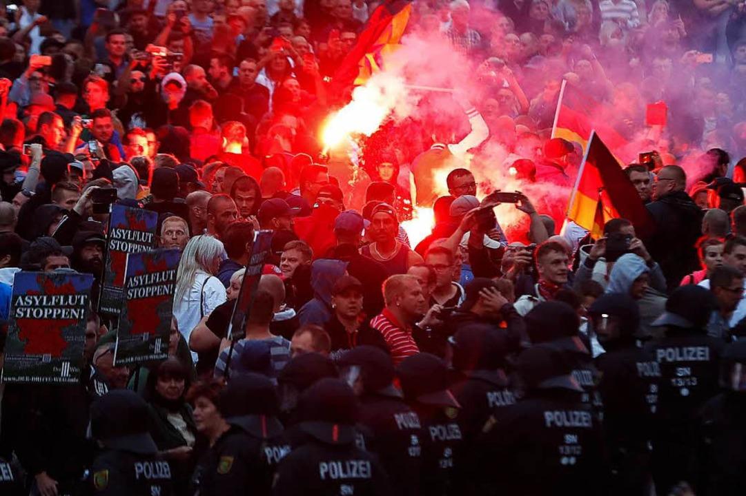 Mit Pyrotechnik und Deutschlandfahnen:...monstranten am Montagabend in Chemnitz  | Foto: AFP/dpa