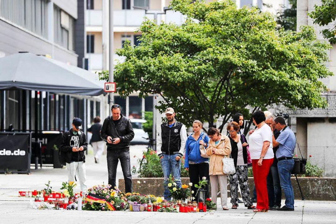 Am Dienstag stehen Passanten am Tatort, an dem zahlreiche Blumen liegen.  | Foto: dpa