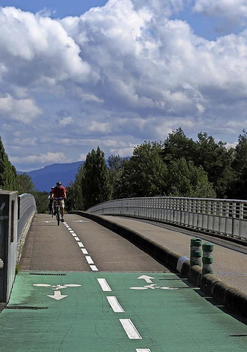 Radelnd wird der Rhein überquert. Auf ...rtet Fragen zur Streckenführung (r.).   | Foto: Philipp