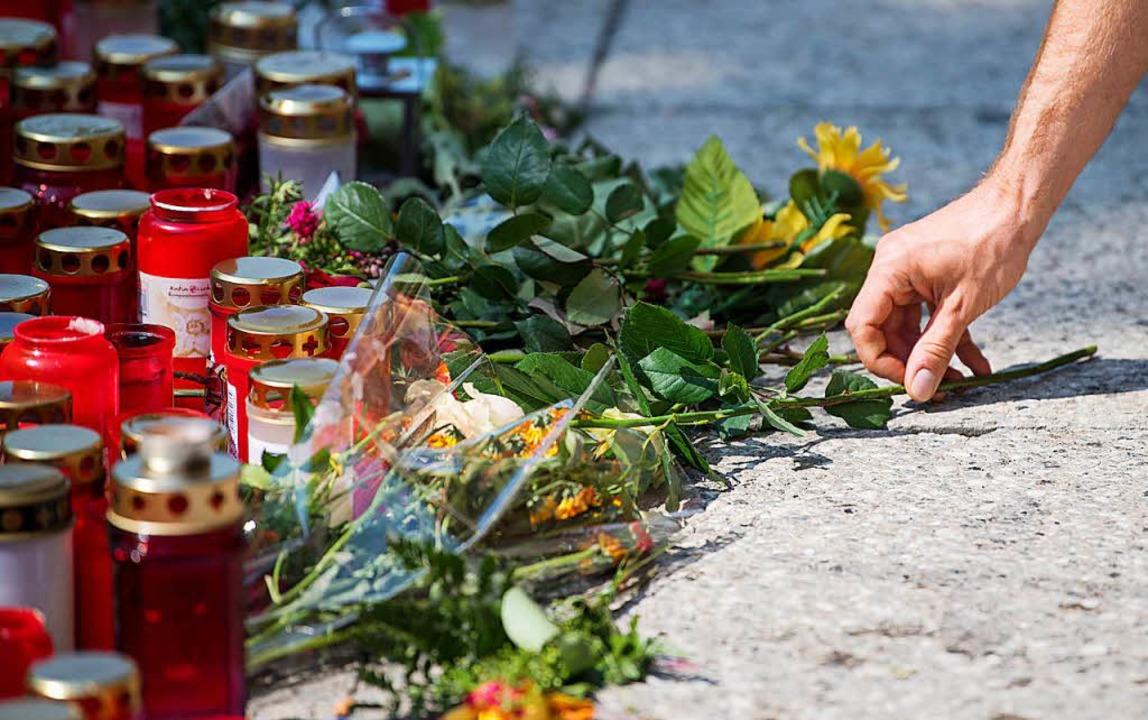 Menschen legen Blumen am Ort nieder, w...einen der Täter veröffentlicht wurde.   | Foto: DPA