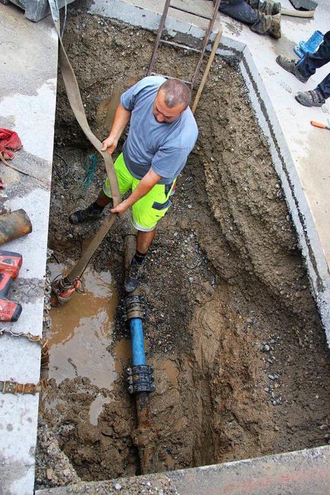 Ausgetretenes Wasser wird mit einem Schlauch aus der Baugrube abgepumpt.  | Foto: Horst David