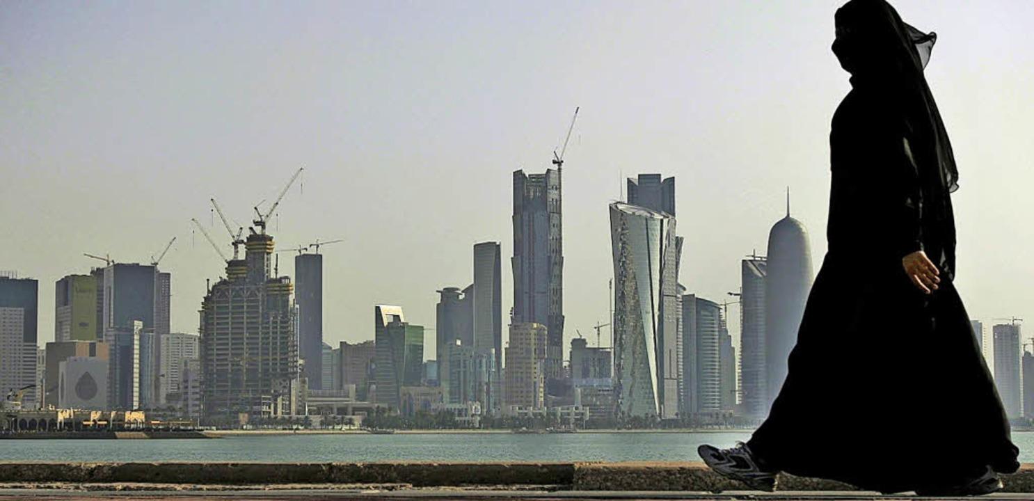 Eine Frau spaziert vor der Skyline der Stadt Doha in Katar.     Foto: DPA