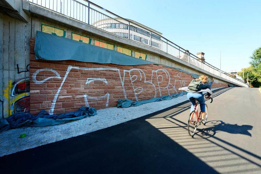Die Mauern unter der neuen Brücke werd...n verblendet – und vollgesprüht.  | Foto: Ingo Schneider