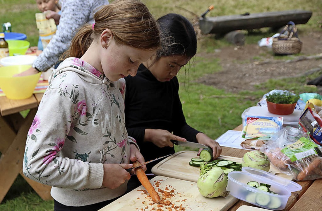 Ida und Lena säubern Karotten und schnibbeln sie dann klein.  | Foto: Eva Korinth
