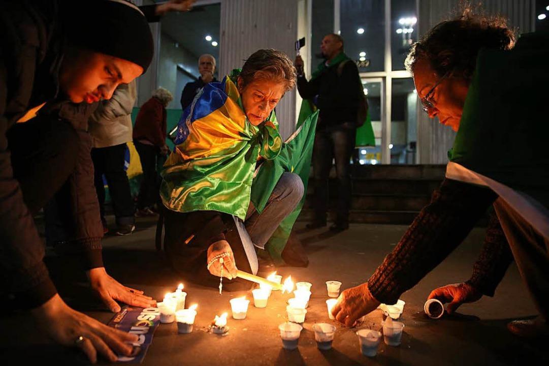 Nach der Messerattacke  zünden Menschen Kerzen für Jair Messias Bolsonaro an.   | Foto: DPA
