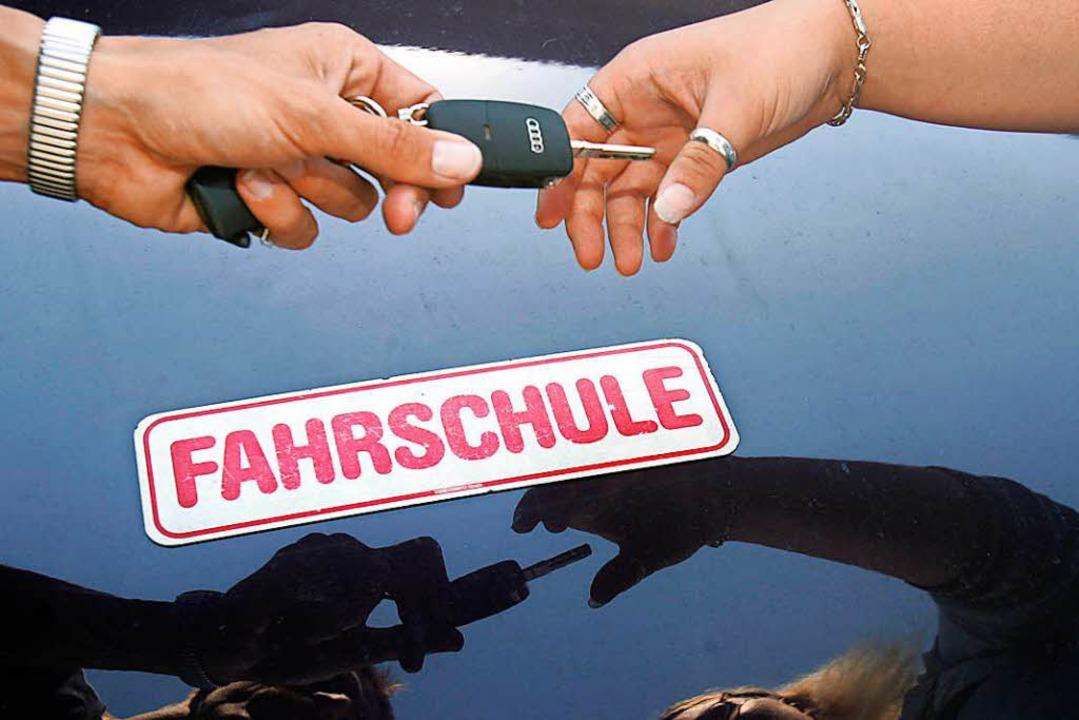 Eine Fahrschülerin erhält den Autoschlüssel zum Fahrschulauto.  | Foto: dpa