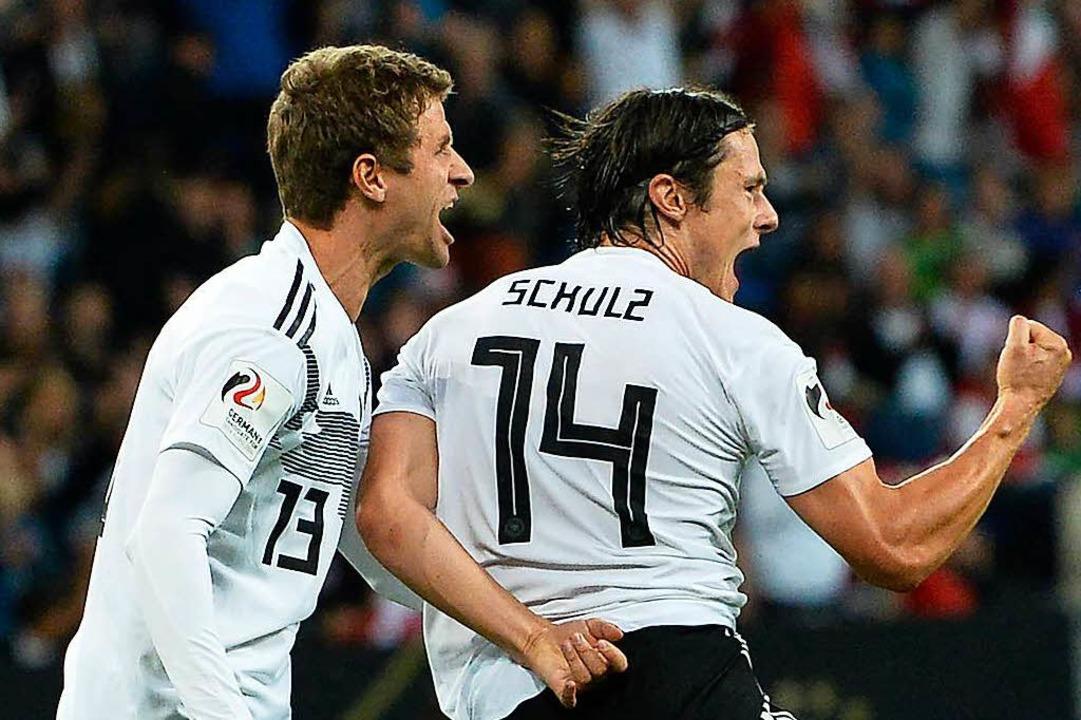 Nico Schulz (rechts) freut sich mit Thomas Müller über den Siegtreffer.    Foto: AFP