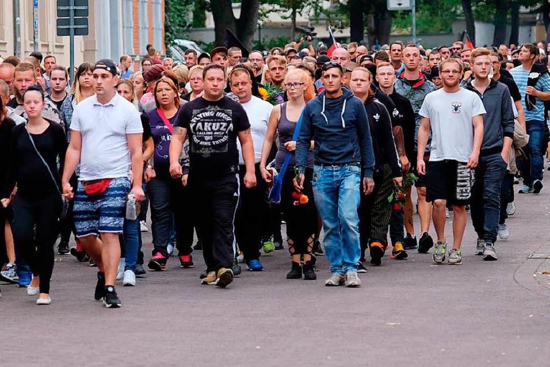 Teilnehmer des Trauerzugs durch Köthen...Männergruppen ums Leben gekommen ist.   | Foto: DPA