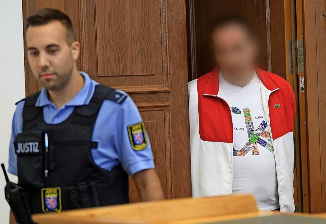 Der Angeklagte (rechts) wird  in den Gerichtssaal geführt.   | Foto: dpa