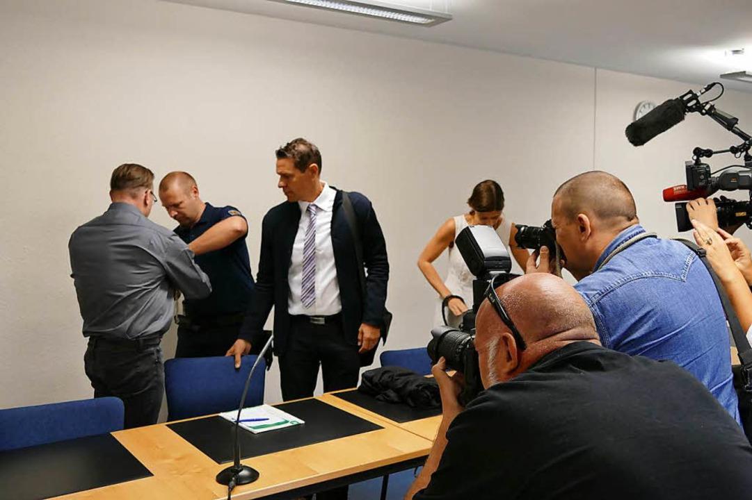 Zum Prozessauftakt wird der Angeklagte in Handschellen in den Saal geführt.  | Foto: Mark Alexander