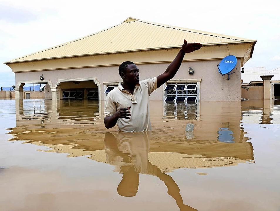 Alles unter Wasser: ein Mann vor seinem Haus in der Stadt Lokoja   | Foto: AFP