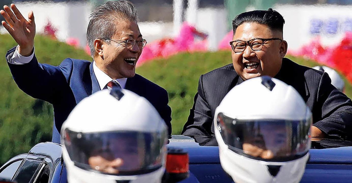 Moon (links) und Kim jubeln bei der Fahrt durch in Pjöngjang.     Foto: afp