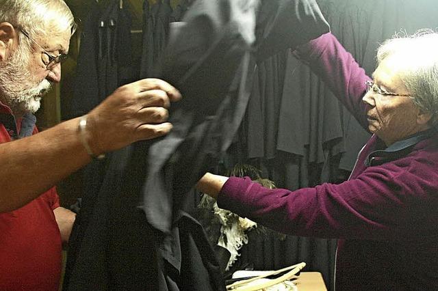 Darsteller hängen Kleider an den Haken