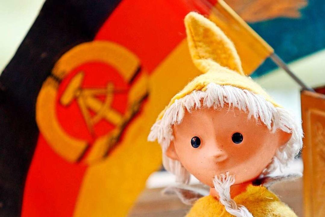 Im Hintergrund ist die Flagge der ehem..., im Vordergrund das DDR-Sandmännchen.  | Foto: Jan Woitas