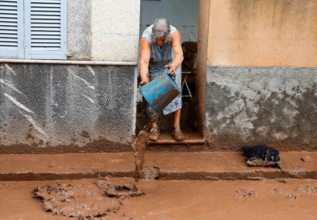 Nach dem Unwetter: Eine Anwohnerin bef...Zwei Deutsche sidn wahrscheinlich tot.  | Foto: dpa