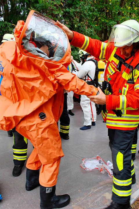 Chemikalienschutzanzugs-Träger brauchen Hilfe beim Anziehen.  | Foto: Erich Krieger