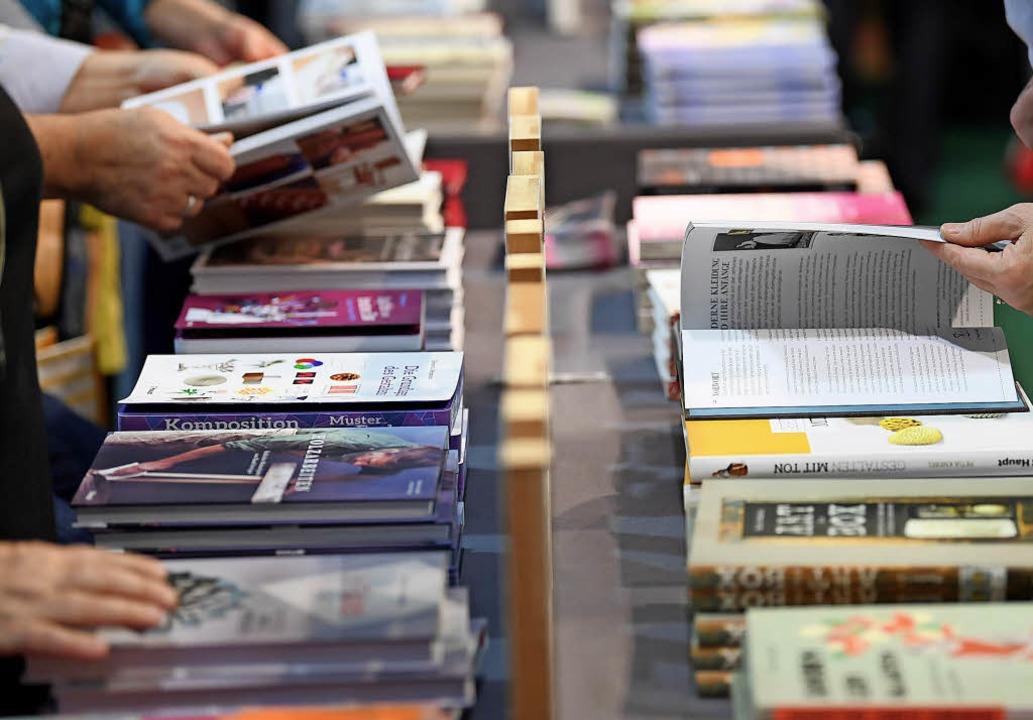 Die Messebesucher blättern in Büchern.  | Foto: dpa