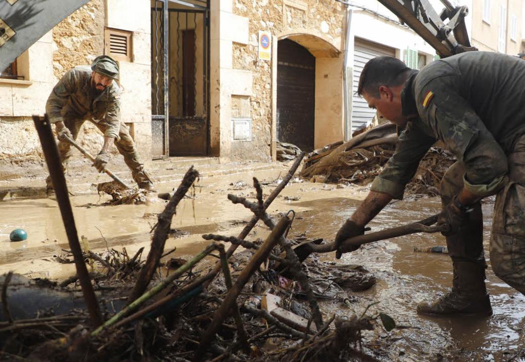 Spanische Soldaten reinigen eine verschlammte Straße.  | Foto: dpa