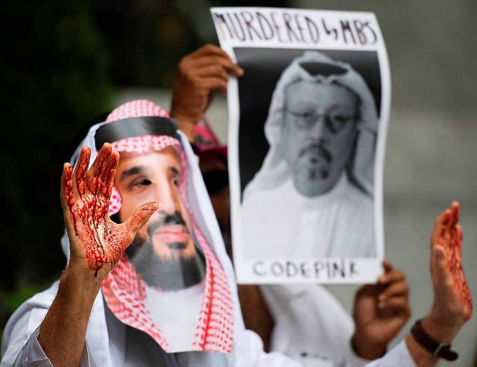 Kunstblut klebt an den Händen der Demo...ägt die Maske des saudischen Prinzen.   | Foto: AFP