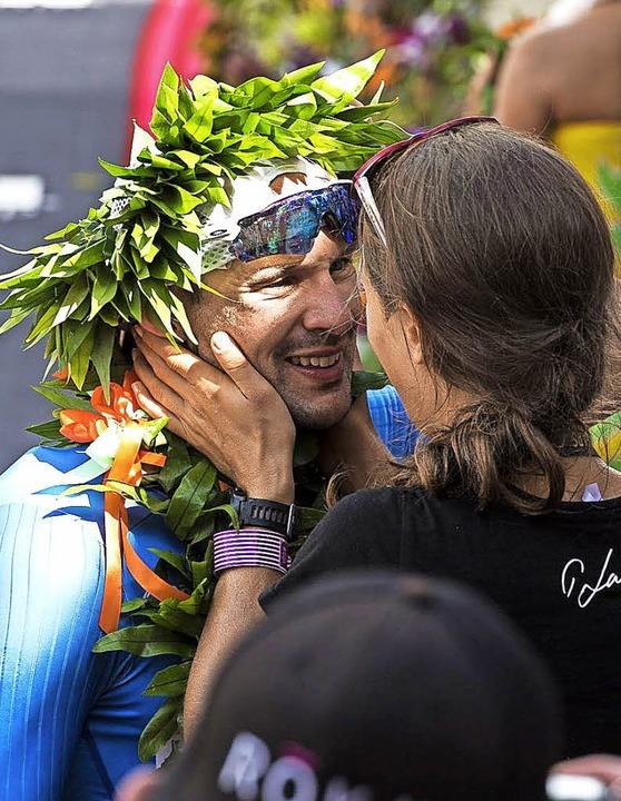 Patrick Lange macht mit Siegerkranz seiner Freundin einen Heiratsantrag.    Foto: dpa