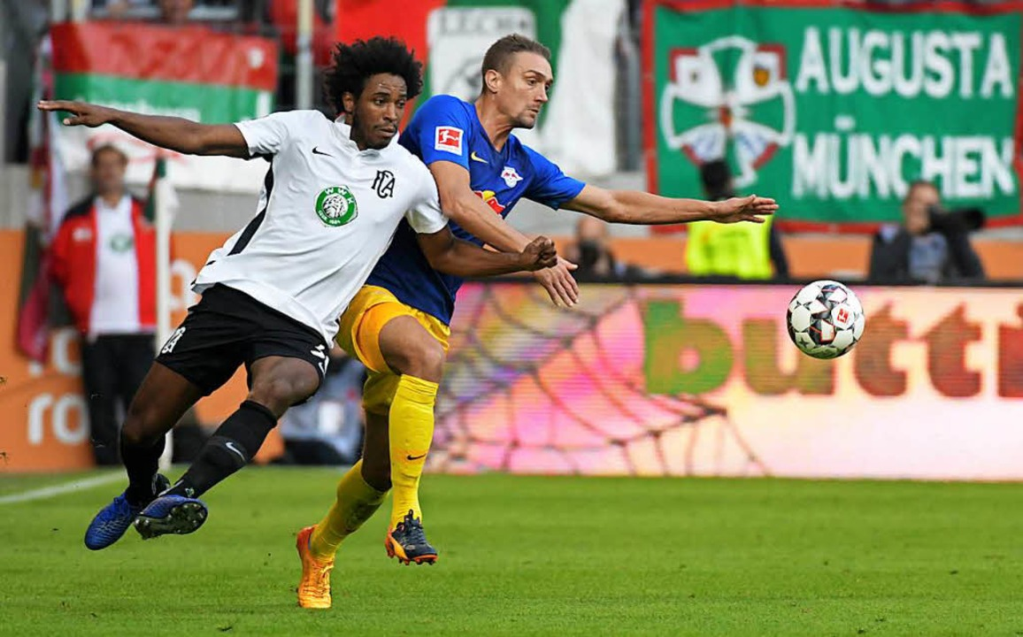 FC Augsburg - RB Leipzig:  Augsburgs C...n Stefan Ilsanker (Leipzig) abgedrängt    Foto: dpa