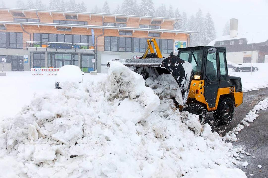 Ein Radlader räumt auf dem Feldberg de...ch gefallenen Schnee von einer Straße.  | Foto: dpa