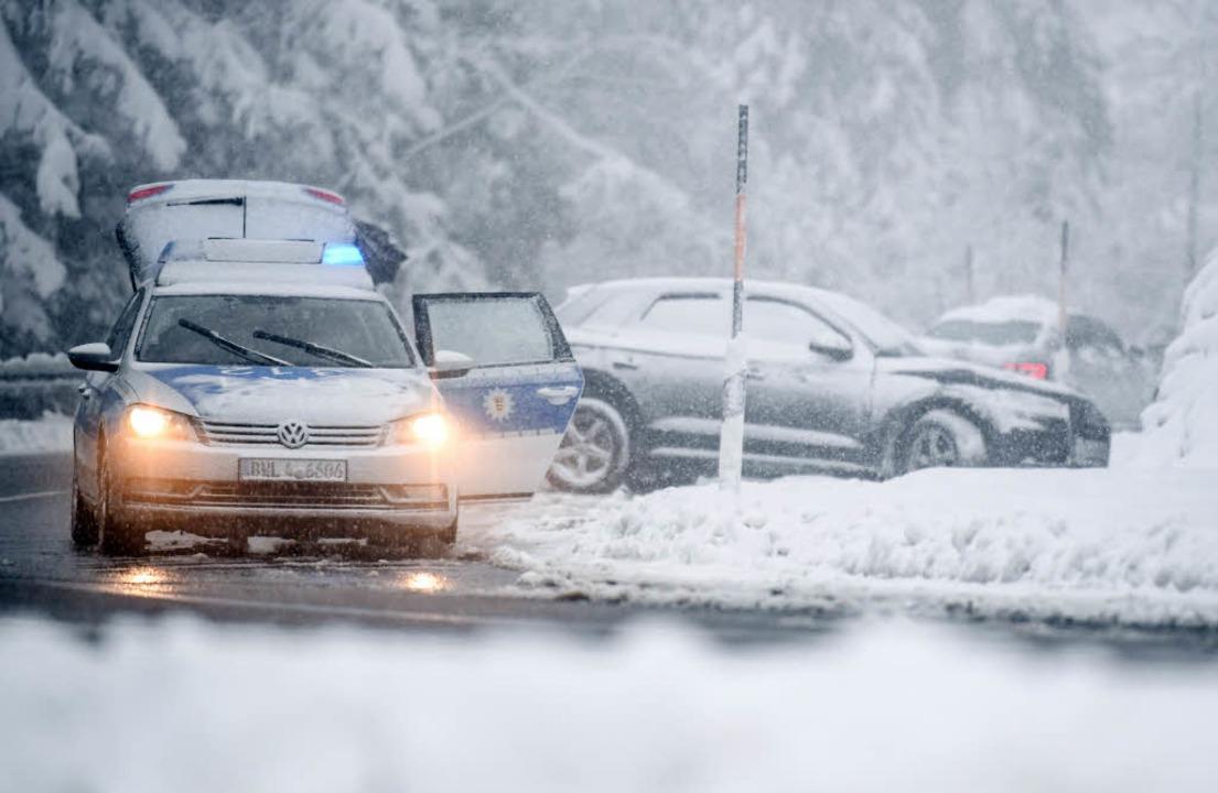 Ein Polizeifahrzeug steht auf dem Feld... rund 15 Zentimeter Neuschnee gegeben.  | Foto: dpa