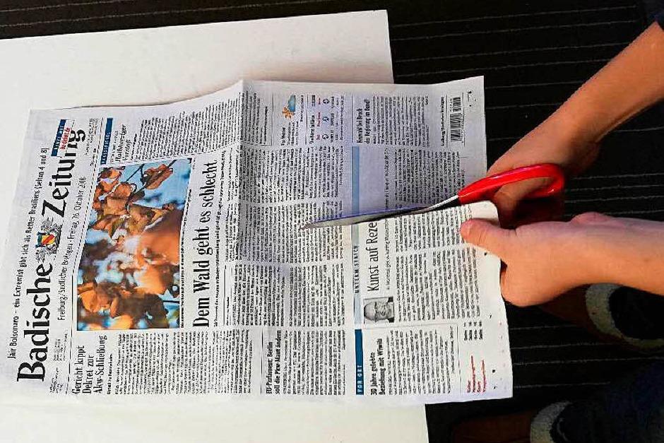 Zuallererst brauchst du alte Zeitungen. Schneide Zeitungsblätter der Länge nach durch. (Foto: Sylvia Knickrehm)