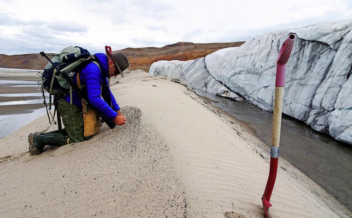 Ein Forscher sammelt Proben vor dem Hi...rater unter einem Eisschild entdeckt.   | Foto: dpa