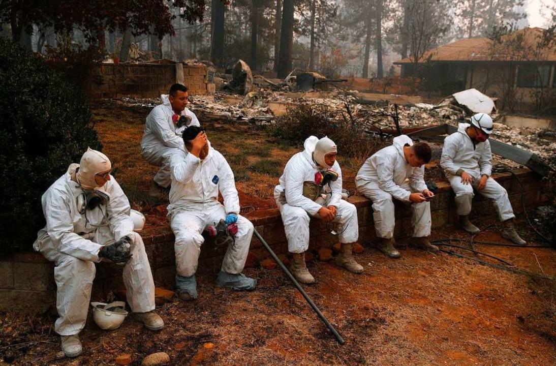 Mitglieder der California Army Nationa... nach Leichen in abgebrannten Häusern.  | Foto: dpa