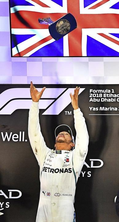 Der Brite Lewis Hamilton wirft den Sie...nd fängt ihn anschließend wieder auf.   | Foto: AFP