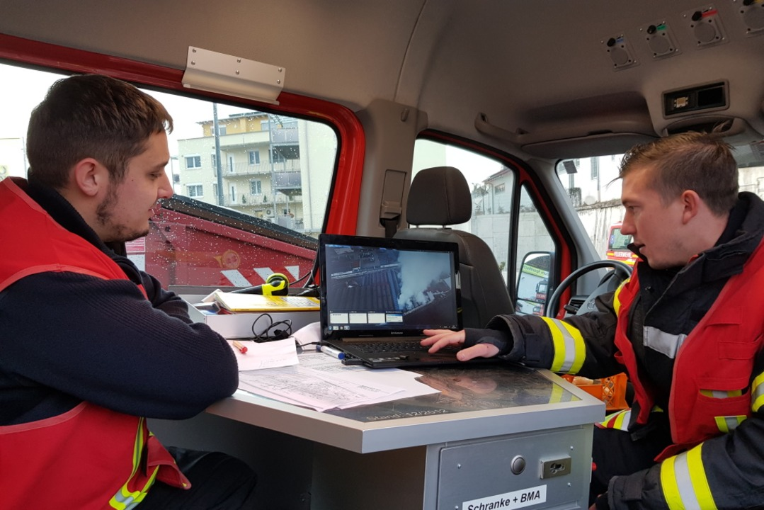 Zwei Feuerwehrmänner begutachten die Drohnenaufnahmen am Laptop im Einsatzwagen.  | Foto: Felix Held