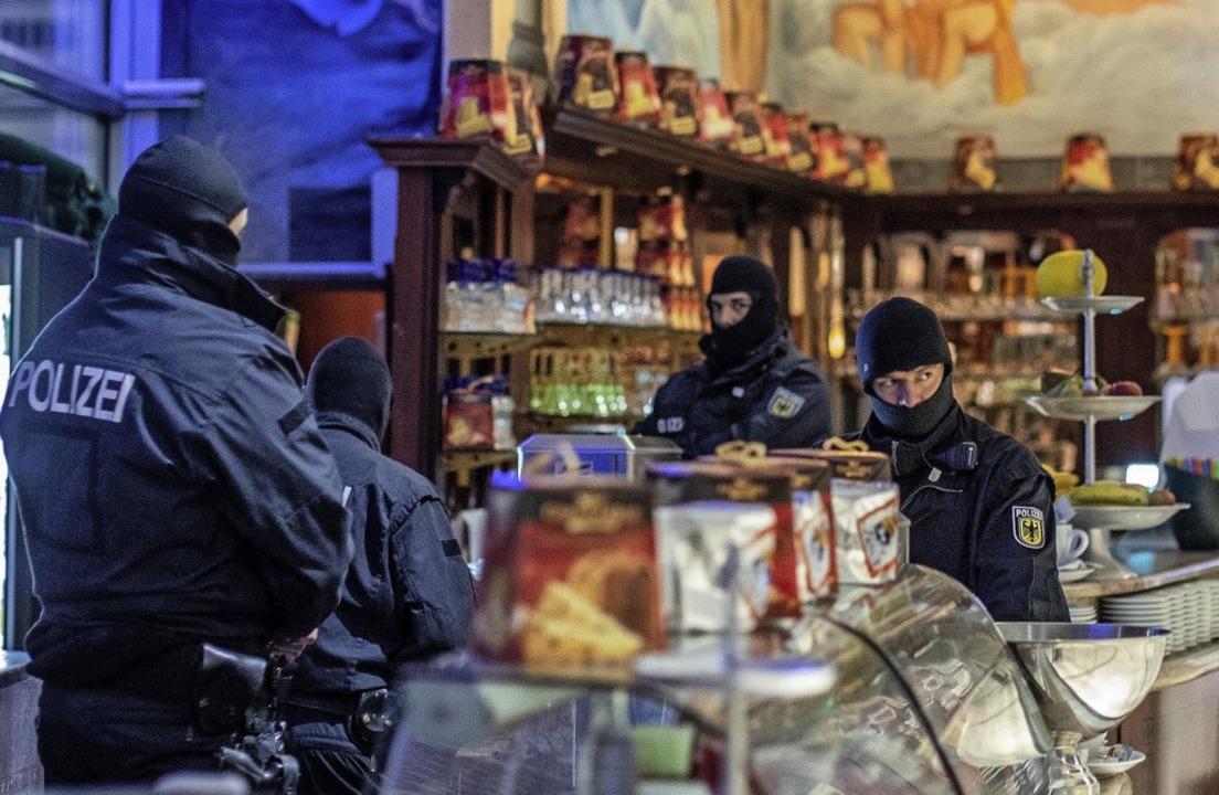 Polizisten stehen in einem Eiscafé  in...onal halten und austauschen zu können.  | Foto: dpa