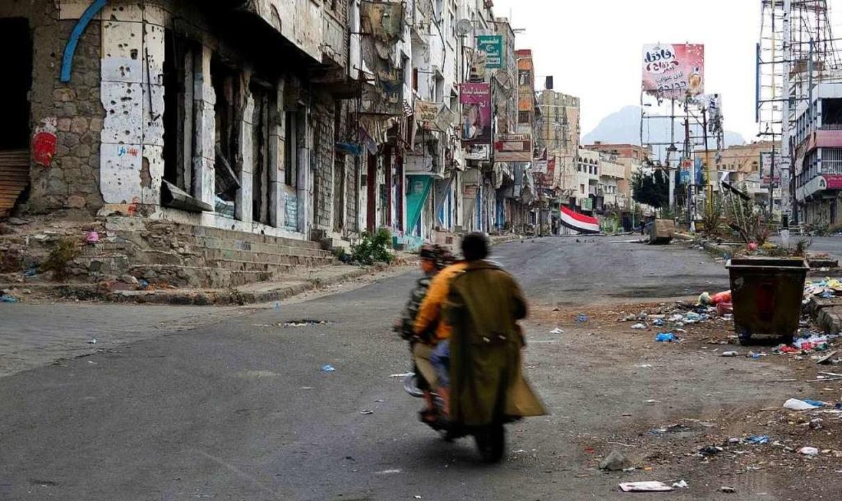 Männer fahren auf einem Zweirad durch ... zerstörten Straßenzug in Taiz, Jemen.    Foto: dpa