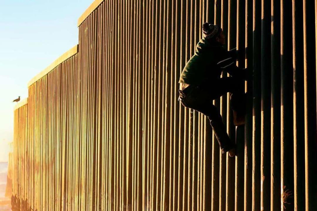 Ein Migrant aus Honduras versucht den ...erikanischen Grenzzaun zu überwinden.   | Foto: AFP