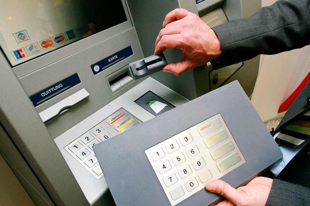 Ein Mitarbeiter der Sparkasse Koblenz ...em Geldautomaten die Skimming-Technik.  | Foto: dpa
