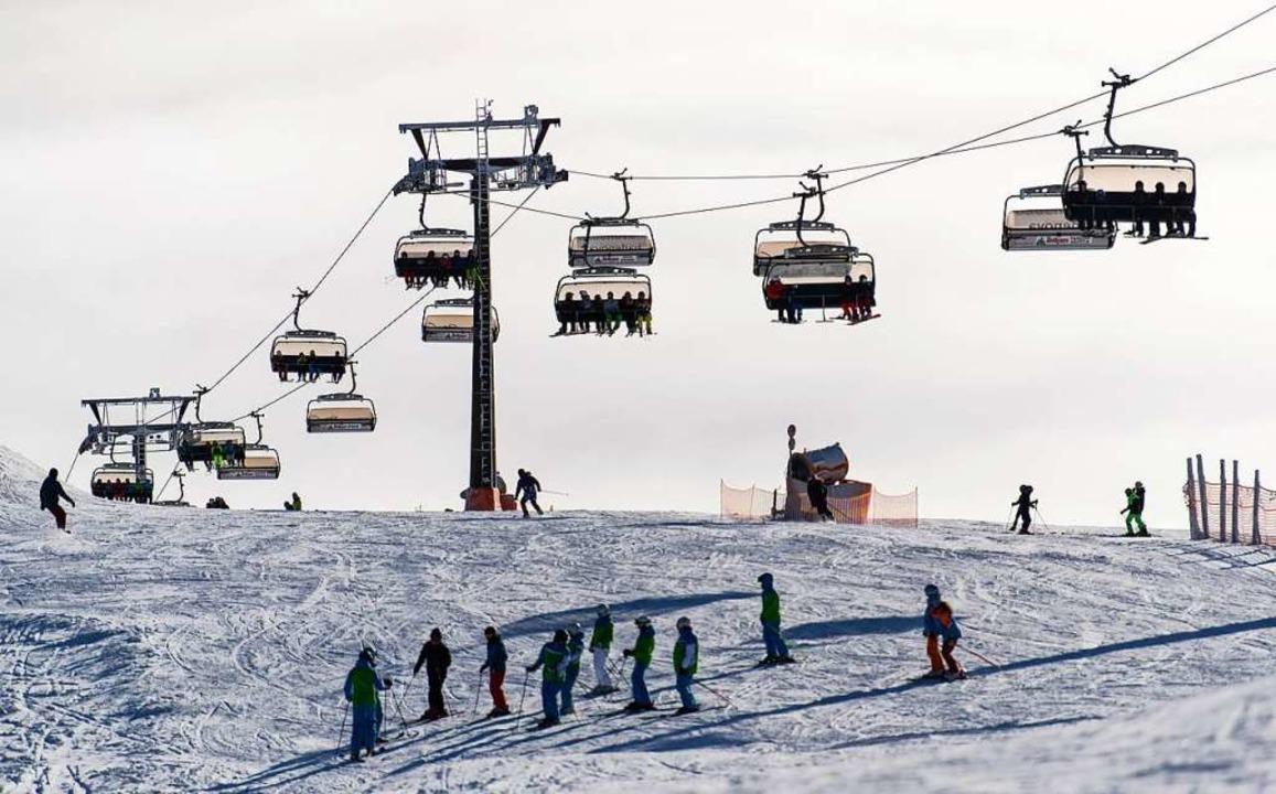 Skifahrer fahren unter einem Sessellift über die Piste.    Foto: dpa