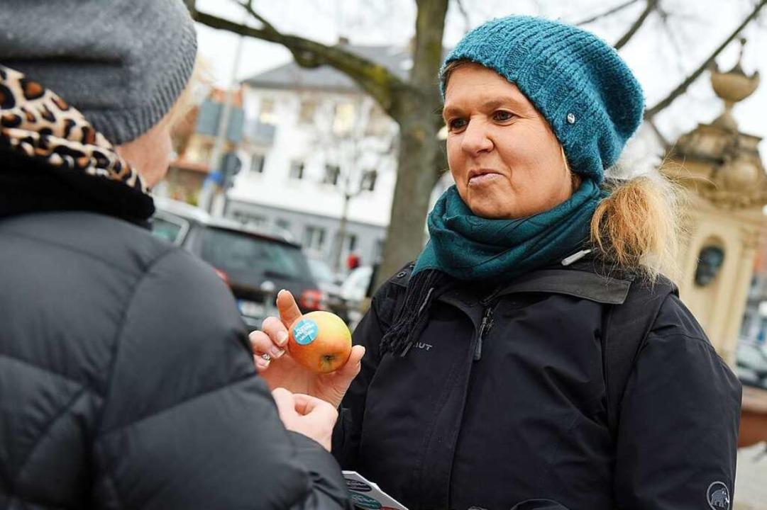 SPD-Stadträtin Karin Seebacher verteil...aslacher Dorfbrunnen  Äpfel und Infos.  | Foto: Rita Eggstein