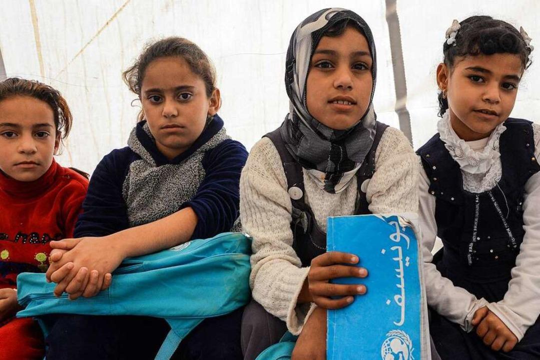Diese Flüchtlingsmädchen im Irak haben Schulsachen vom UNHCR bekommen.  | Foto: AFP
